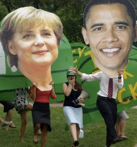 Merkel and Obama dance with green hard hats